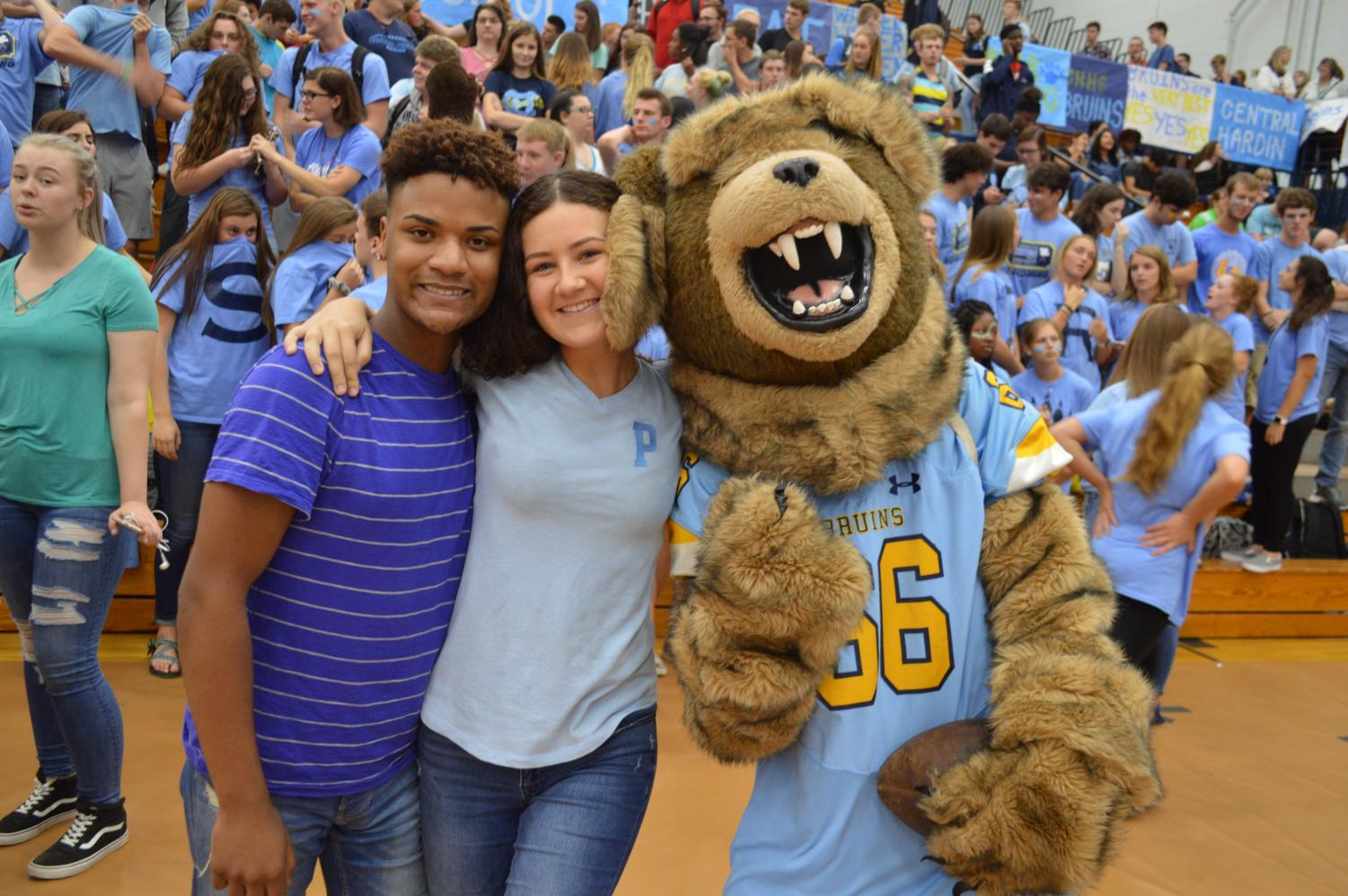 School Colors: Deion Lindsey and Rachel Cummins take a picture with the mascot while dressed in their class colors.