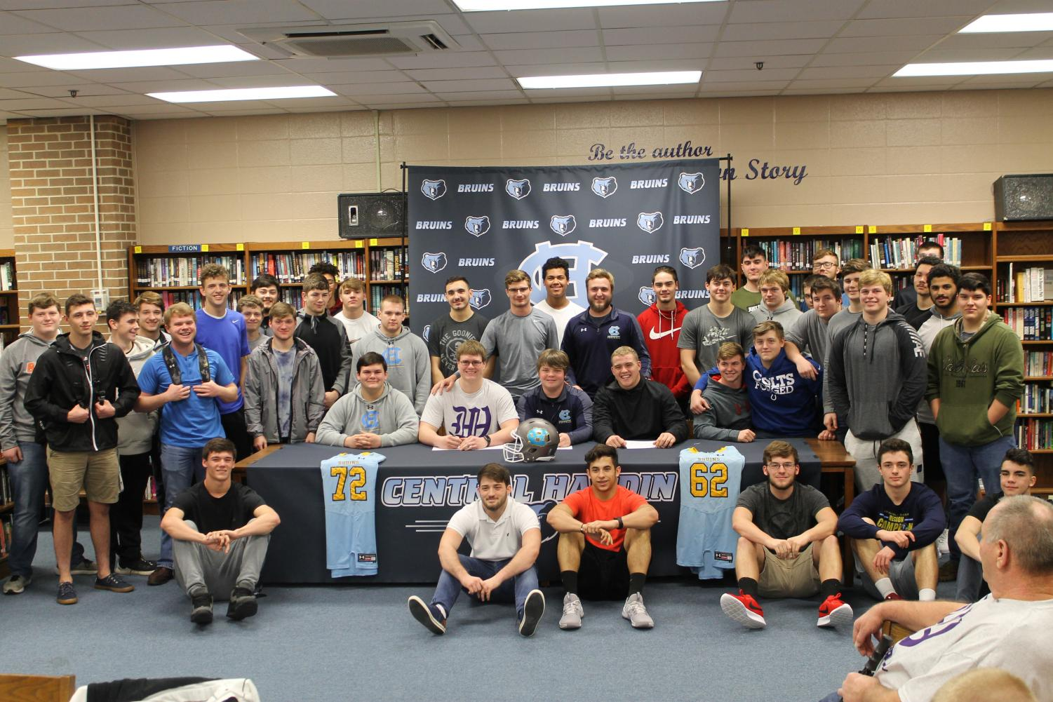 Senior+football+players+Zach+Jones+and+Chase+Conner+sign+with+Kentucky+Wesleyan+College+on+Feb.+6%2C+surrounded+by+their+teammates%2C+coaches%2C+and+families.