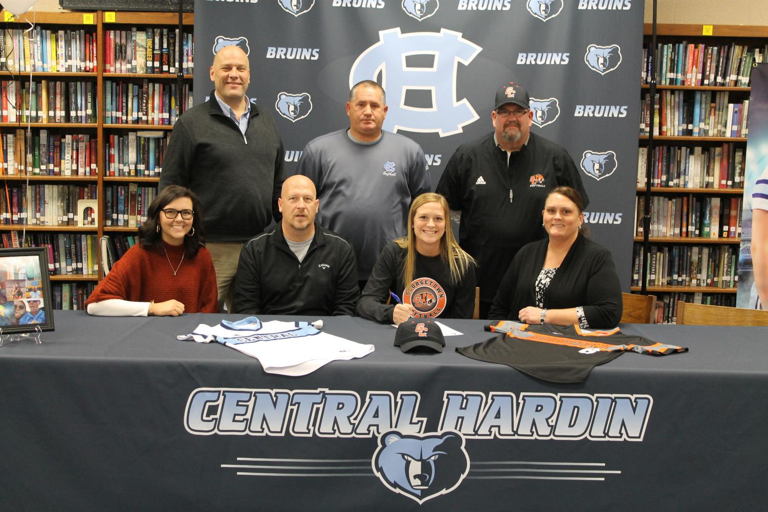 Peyton Beger signs with Georgetown College Softball on Nov. 28, surrounded by Jordin and Andy Beger (left) and Lori Beger (right). Back row: principal Tim Isaacs, CHHS coach Jamie Goodman, and Georgetown coach Thomas Thornton.
