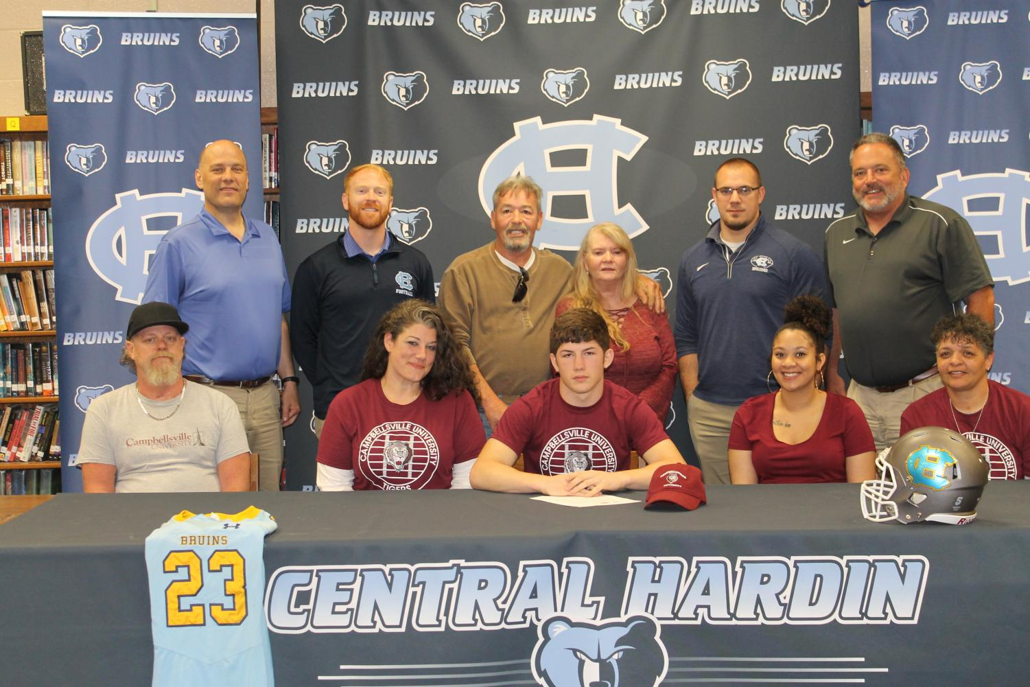 Chris+Bellin+signs+with+the+Campbellsville+University+football+program+on+April+12%2C+surrounded+by+family+and+coaches.