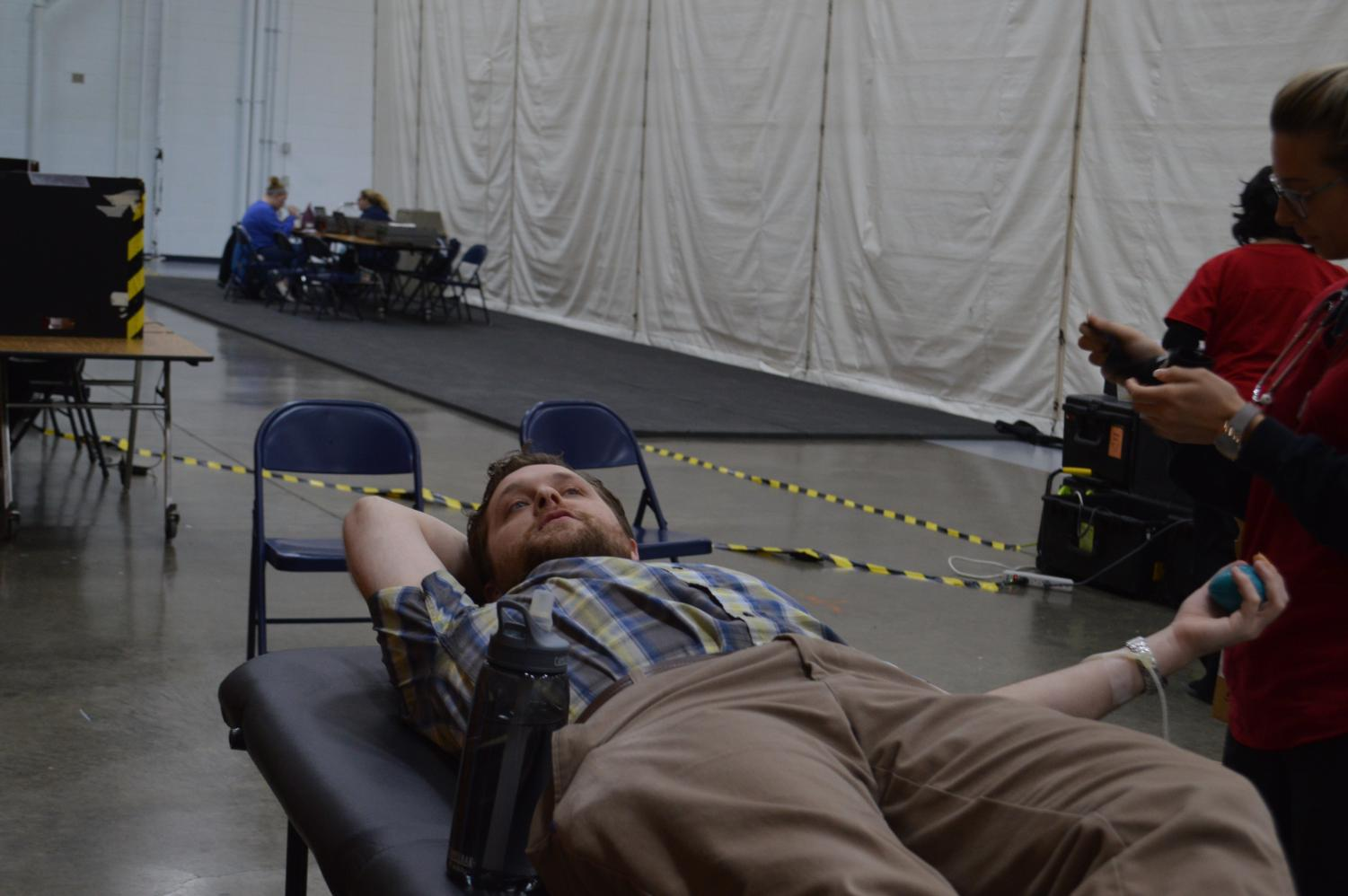 Sophomore+biology+teacher%2C+Jared+Eaton+lays+down+as+he+donates+blood+and+talks+to+students.