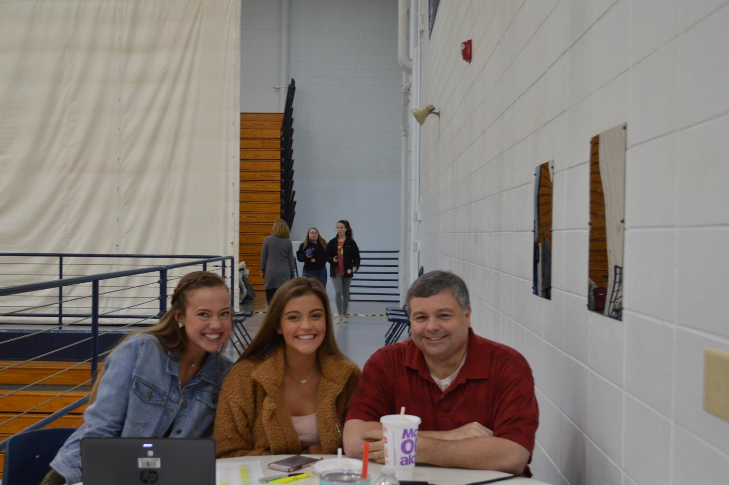 Seniors Kaci Geodde and Ella Lewis sit at the sign in table with Duel Credit History teacher and blood drive sponsor James Sisk.