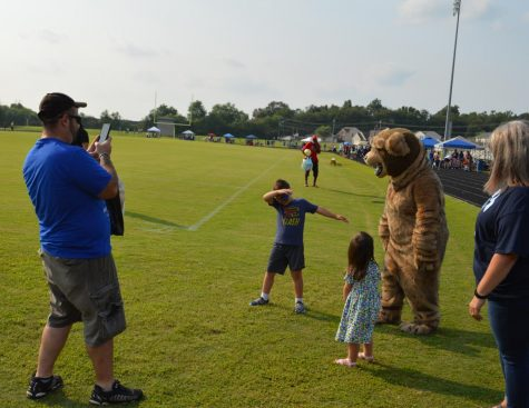 Lakewood Elementary first grader Mason Peters dabs with the Bruin Bear at the Bruin Fest on July 22 at Central Hardin High School as dad  Eric Peters captures the moment and sister Maggie, three years old, looks on.