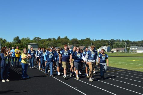 The football team takes their stroll in front of the crowd at the pep rally on Sept. 24. The team went on to defeat Fern Creek 38-14 later that night.